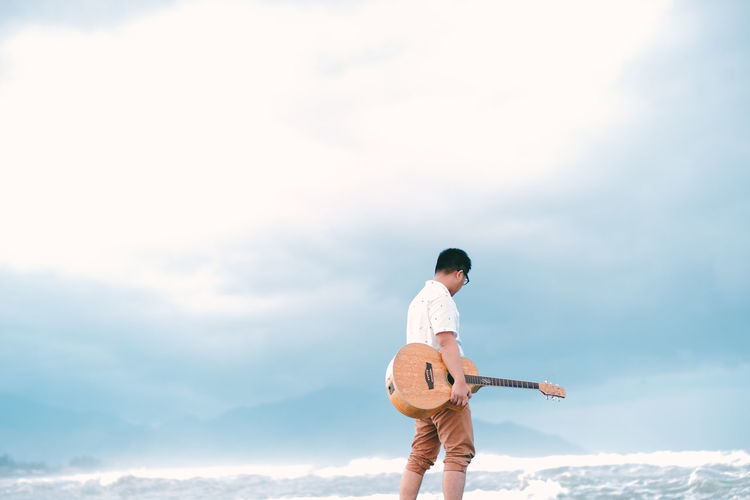 Man holding guitar walking at sea shore against sky