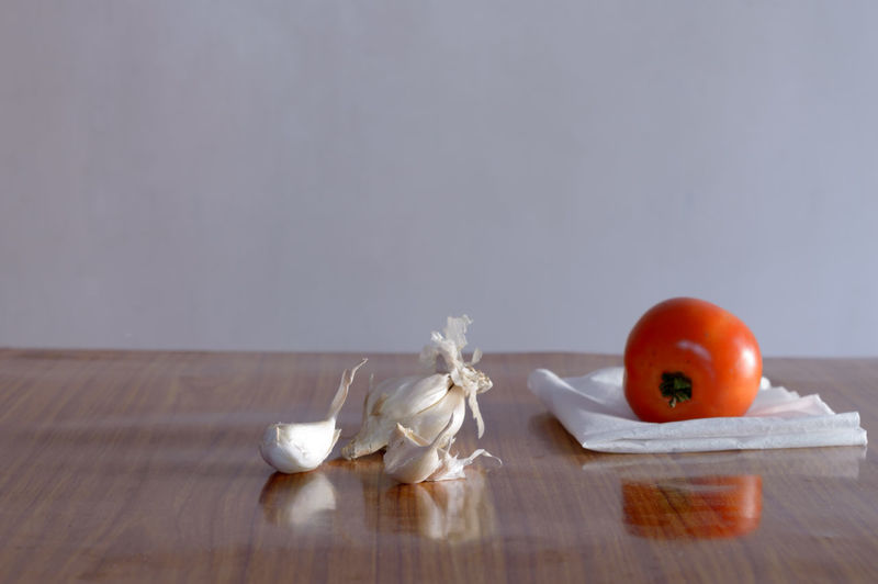 Close-up of apple on table against wall