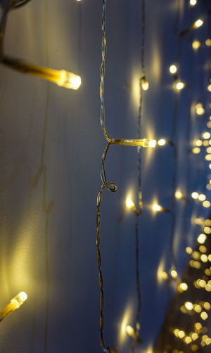 Close-up of illuminated lighting equipment hanging on wall