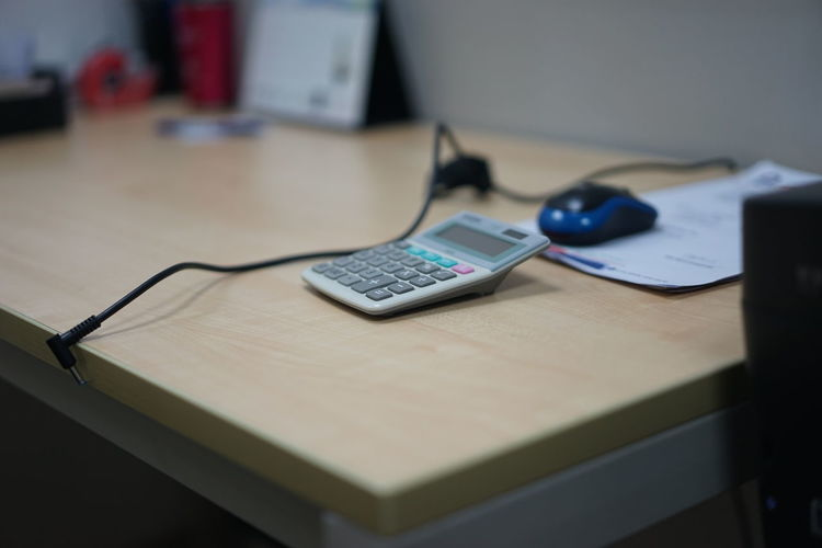 Absence Business Calculator Communication Computer Computer Equipment Connection Corporate Business Desk Eyeglasses  Furniture Home Interior Indoors  Keyboard No People Office Paper Still Life Table Technology Wireless Technology