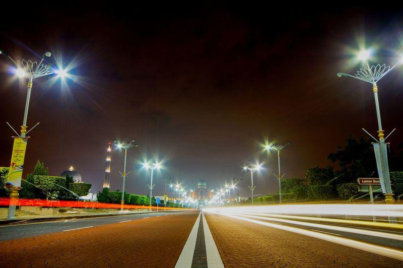 Illuminated light trails on road against sky at night
