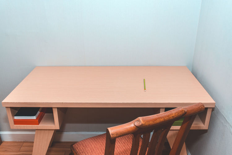 High angle view of empty chair on table against wall