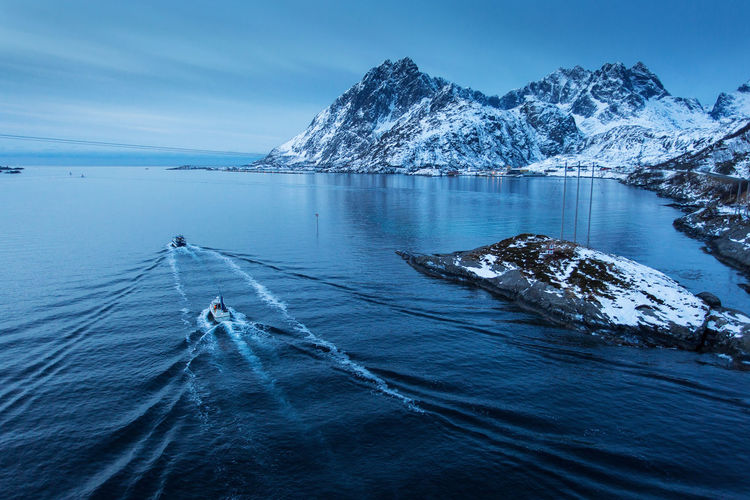 Aerial view boat in sea against mountain