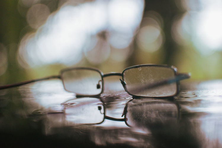 Close-up of eyeglasses on wet table during sunny day