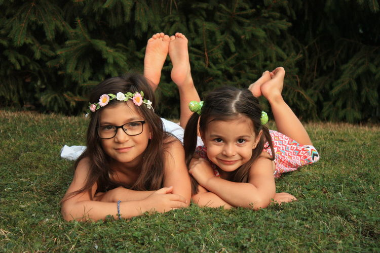 Portrait of sisters lying down on grassy land