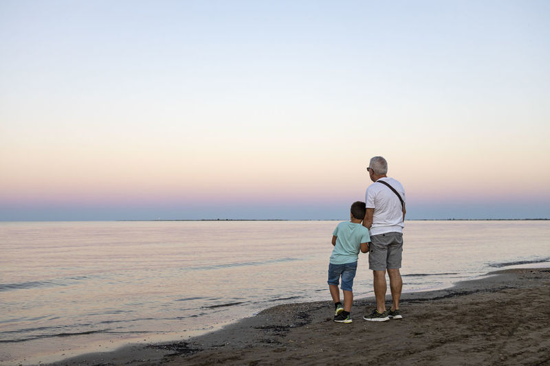 Rear view of grandfather with grandson on beach against sky during sunset