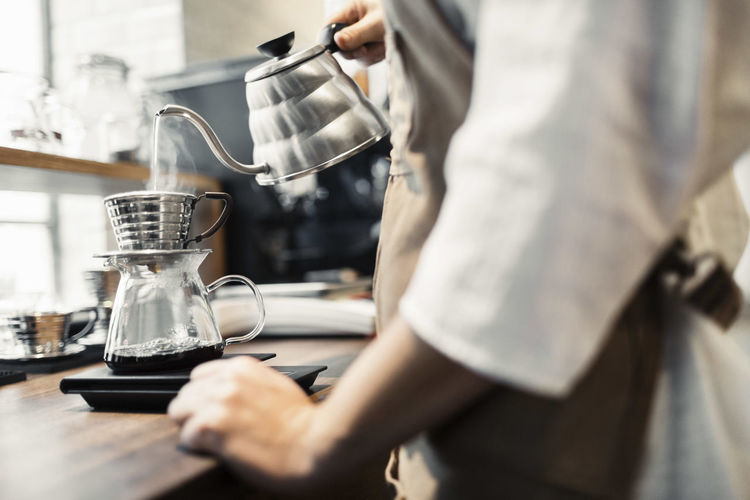 Midsection of man pouring coffee in cup