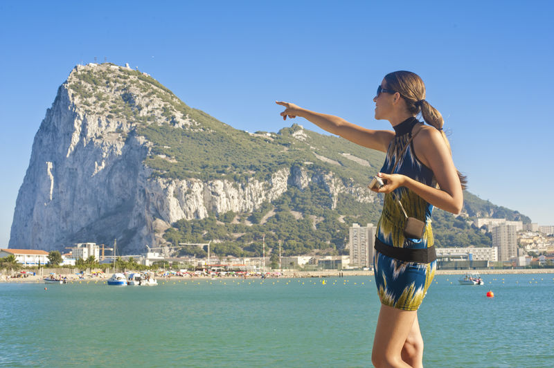 Woman pointing at beach against clear sky