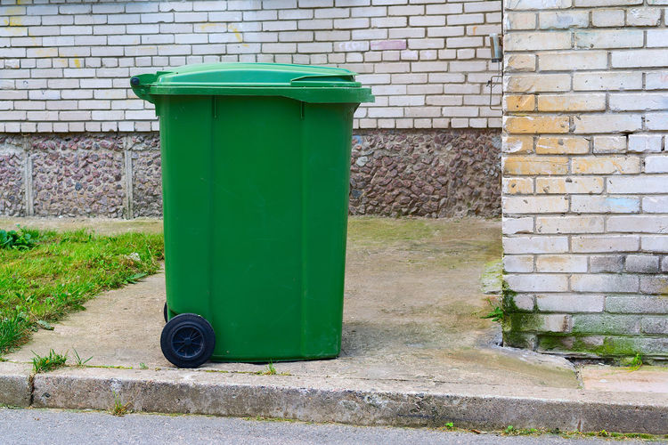 Green garbage can against wall