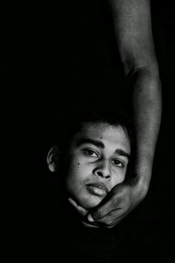 Cropped Hand Holding Head Of Man Against Black Background