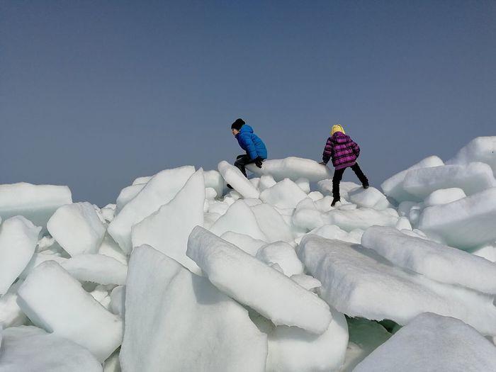 People on ice against sky