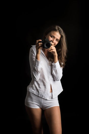 One Person Photography Themes Holding Camera - Photographic Equipment Young Adult Black Background Studio Shot Front View Standing Three Quarter Length Beauty Indoors  Hair Portrait Photographing Adult Activity Women Young Women Technology Beautiful Woman Hairstyle Photographer Shorts