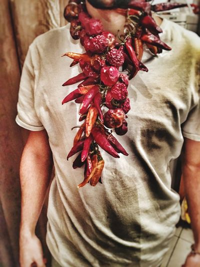 Midsection of man wearing necklace made by red chili peppers