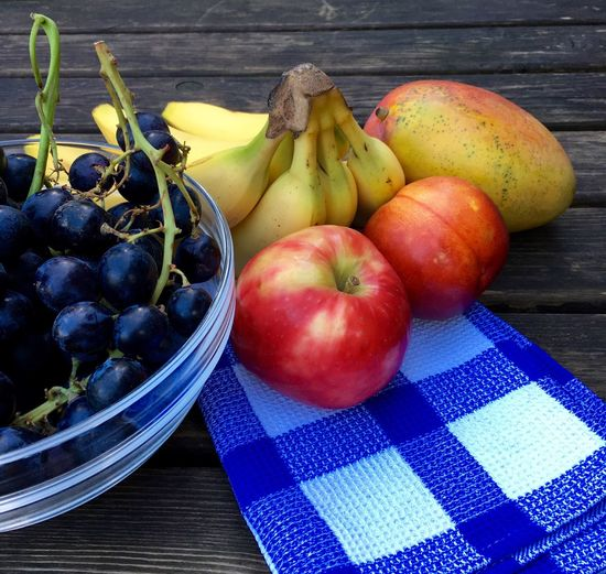 High angle view of fruits and napkin on wooden table
