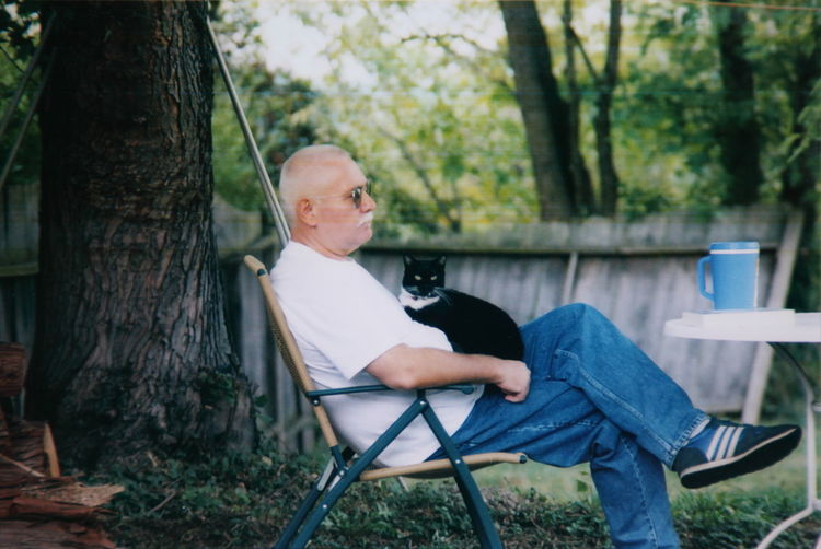Senior Man With Cat Sitting On Chair At Yard