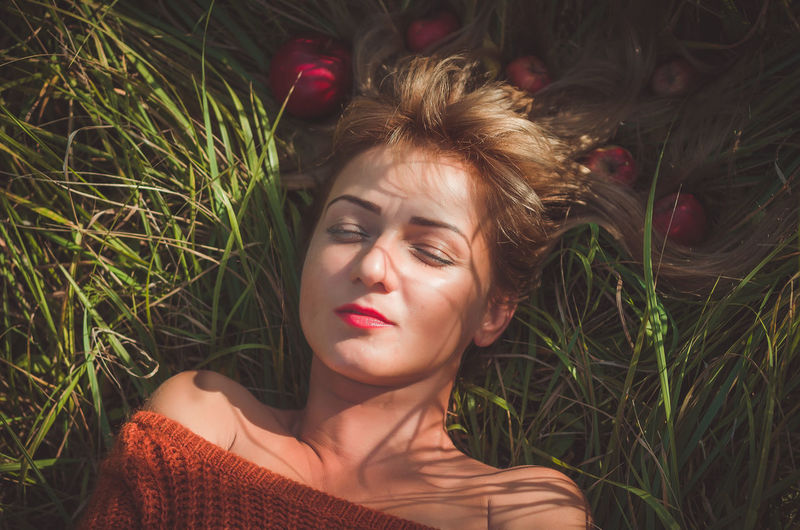 Woman laying on green grass with loose hair with apples Portrait One Person Plant Young Adult Beautiful Woman Lying Down Leisure Activity Young Women Grass Real People Lifestyles Front View Nature Headshot Beauty Women Relaxation Adult Hairstyle Outdoors Contemplation