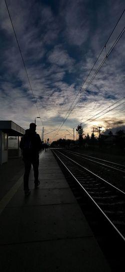 Silhouette people on railroad tracks against sky