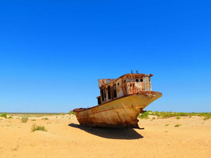 Abandoned boat on sand against clear blue sky