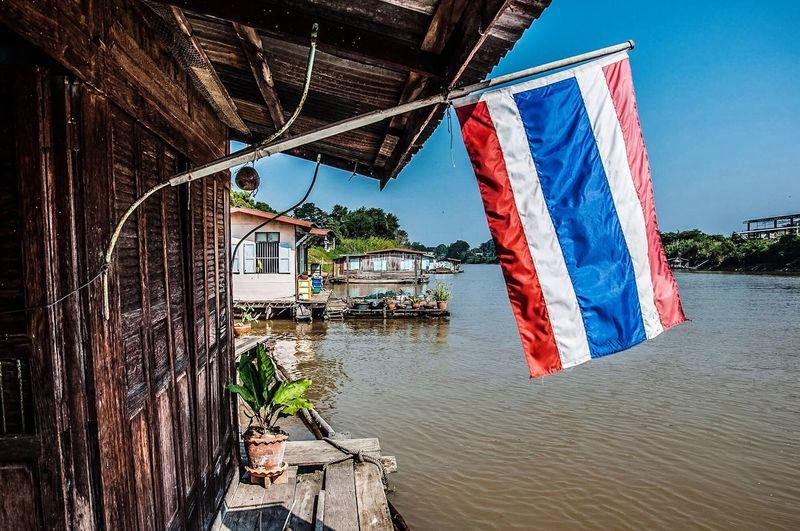 Thai flag on house by river against clear sky