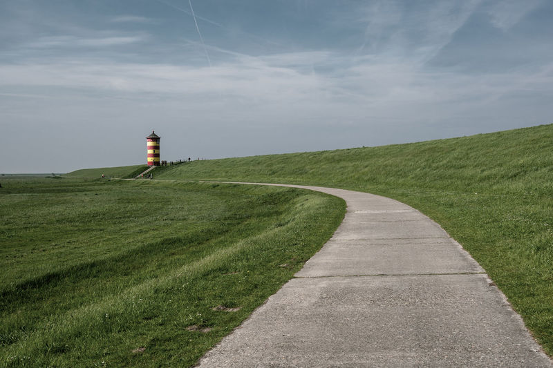 Road Leading Towards Lighthouse Amidst Field Against Sky