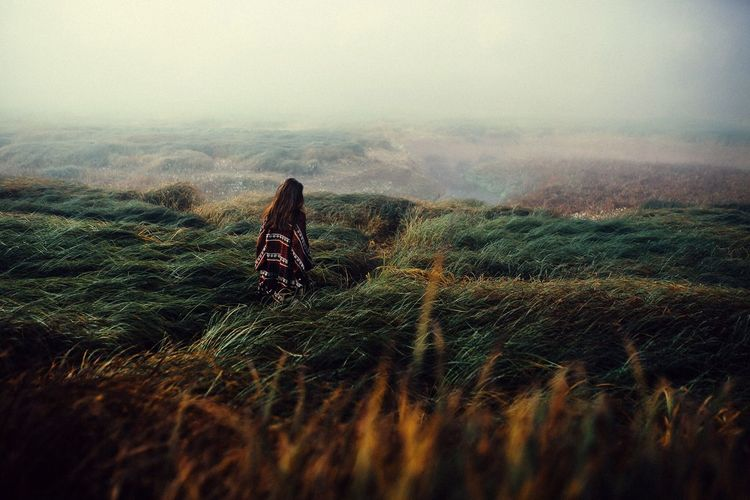 Rear View Of Woman Walking On Grassy Landscape During Foggy Weather