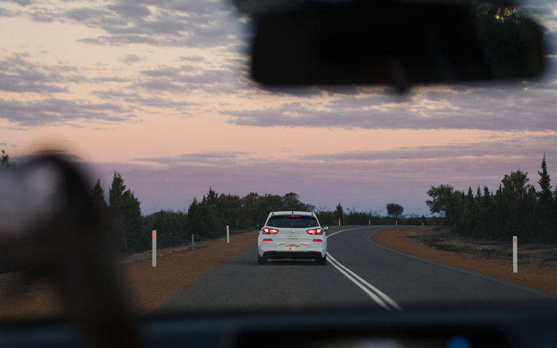 Cars on road against sky seen from car windshield