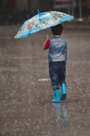 Blue Boots Casual Clothing Childhood Holding Leisure Activity Lifestyles One Person Protection Puddle Rain RainDrop Rainy Season Real People Umbrella Umbrella Revolution Walking Water Weather Wet