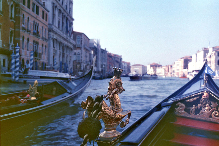 Close-up of gold horse sculpture on gondola in grand canal