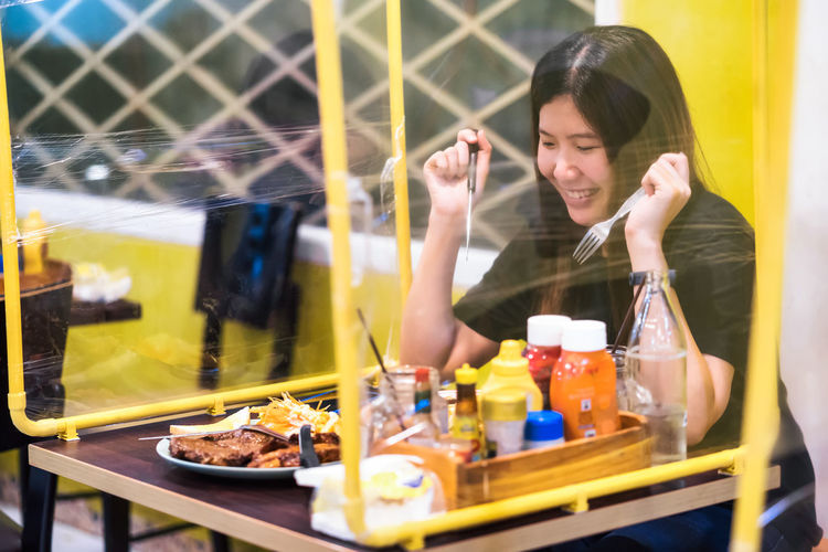Young woman having food in glass container