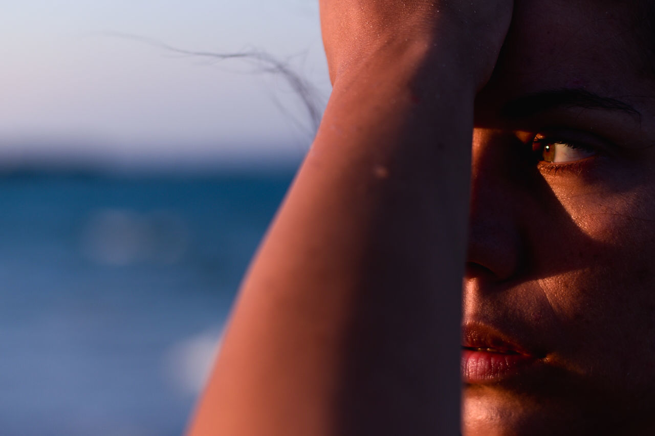 Close-up of thoughtful woman looking away against sea