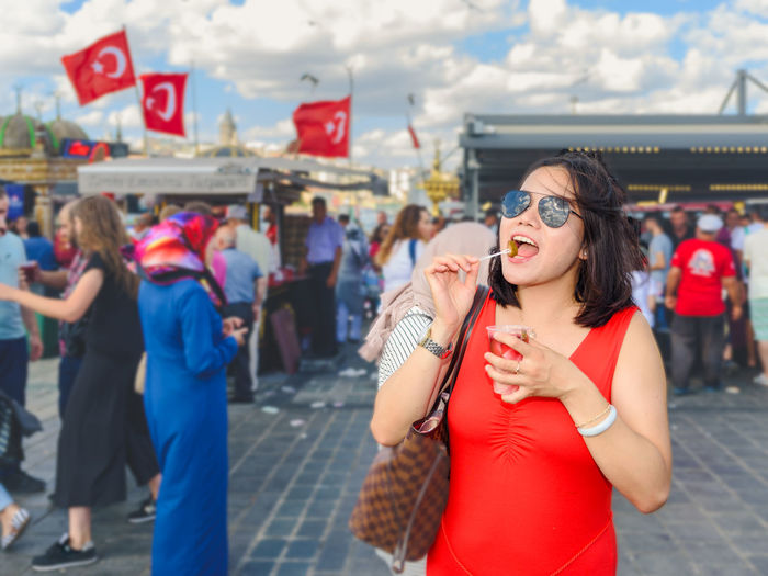 Portrait of woman wearing sunglasses eating pickle while standing in market