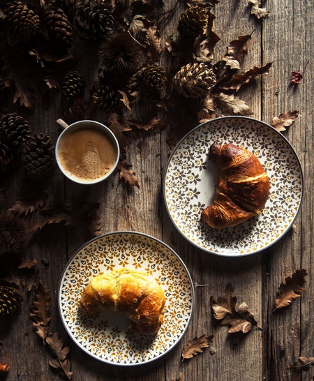 Close-Up Of Coffee With Croissant Served In Plate On Table During