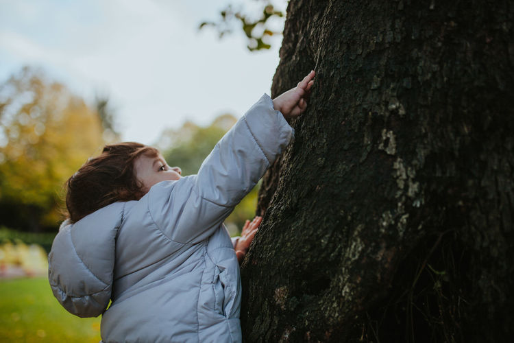 Cute baby girl touching tree in park