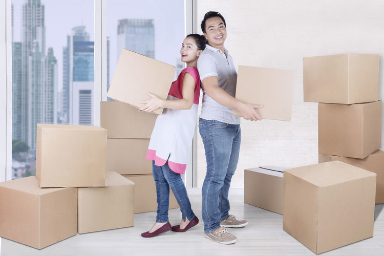 Adult Beginnings Box Boyfriend Cardboard Cardboard Box Casual Clothing Container Couple - Relationship Emotion Girlfriend Heterosexual Couple Holding Home Ownership Men Moving House Positive Emotion Smiling Teamwork Togetherness Two People Women Young Adult Young Couple Young Women