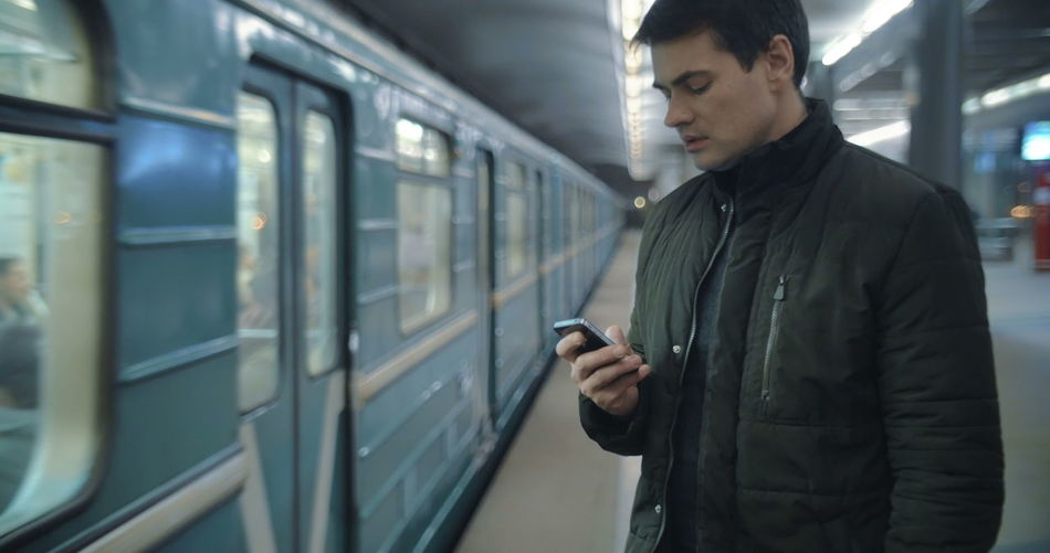 Young man using mobile phone while standing on train