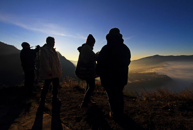 Silhouette people standing on top of mountain at sunset