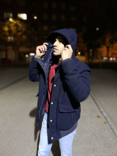 Young man wearing hooded jacket standing on street at night