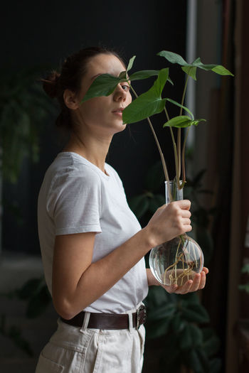 Young woman with arms raised standing against plants