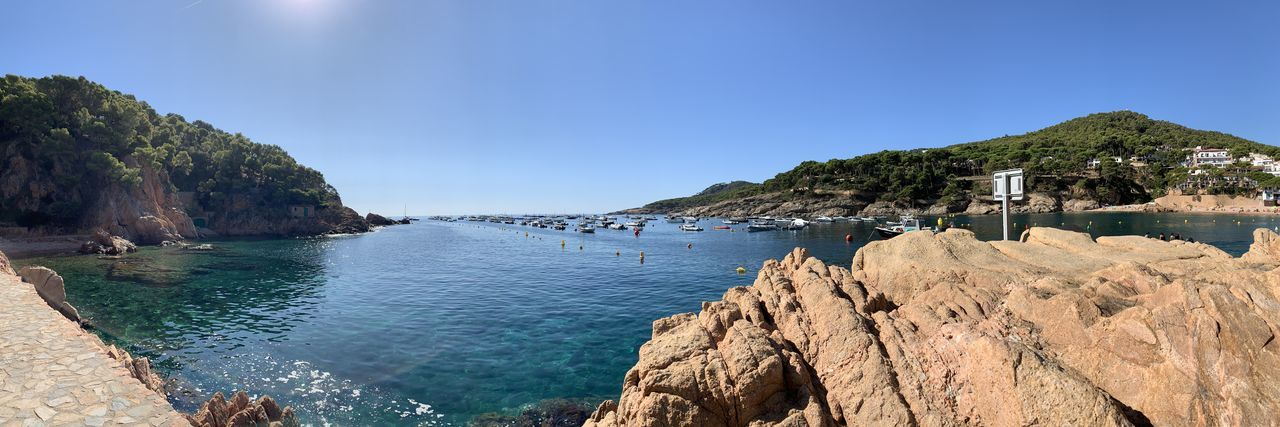 Panoramic view of sea and rocks against clear blue sky