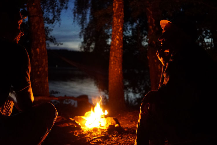 Couple Sitting By Bonfire During Night In Forest
