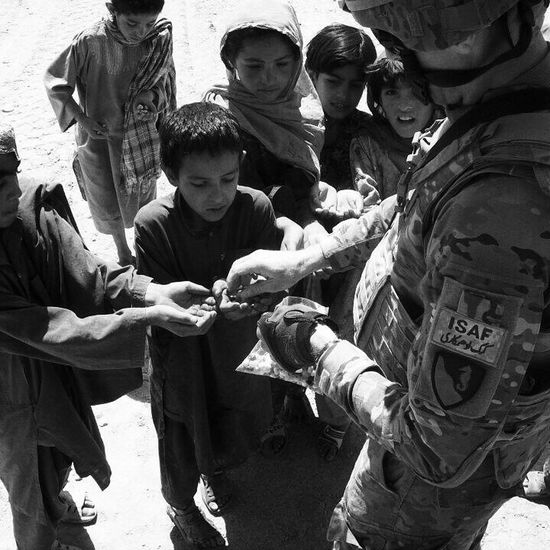 My Favorite Photo I had been deployed to Kandahar province in Afghanistan and at the time my parents owned a candy store back home and had sent me a huge box full of goodies for the Afghani kids. I propped my camera and had it on a time delay and captured this while handing out treats to the kids! Blackandwhite Black & White Kids Military Good Deed