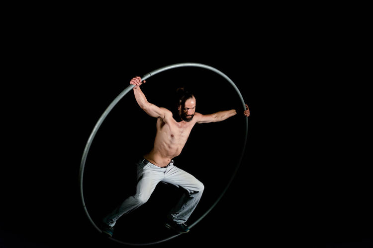 Circus Arms Raised Balance Black Background Circle Copy Space Full Length Geometric Shape Human Arm Indoors  Lifestyles Men Motion One Person Plastic Hoop Shape Shirtless Skill  Strength Studio Shot Young Adult Young Men