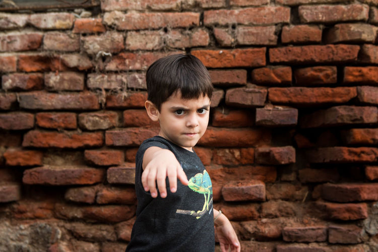 Portrait of boy gesturing against brick wall