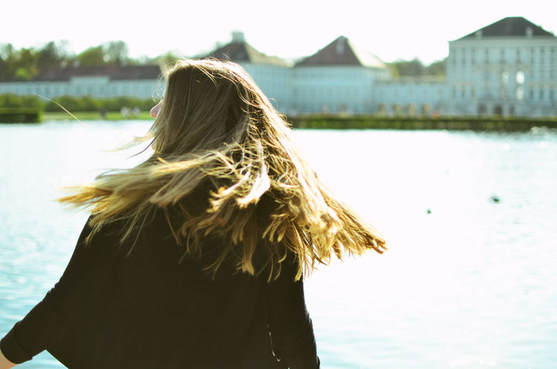 Spinning Hair Hairstyle Rear View One Person Water Real People Long Hair Women Focus On Foreground Lifestyles Standing Leisure Activity Adult Nature Waist Up Day Blond Hair Built Structure Outdoors Warm Clothing Teenager