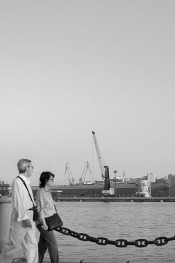 People at harbor against clear sky