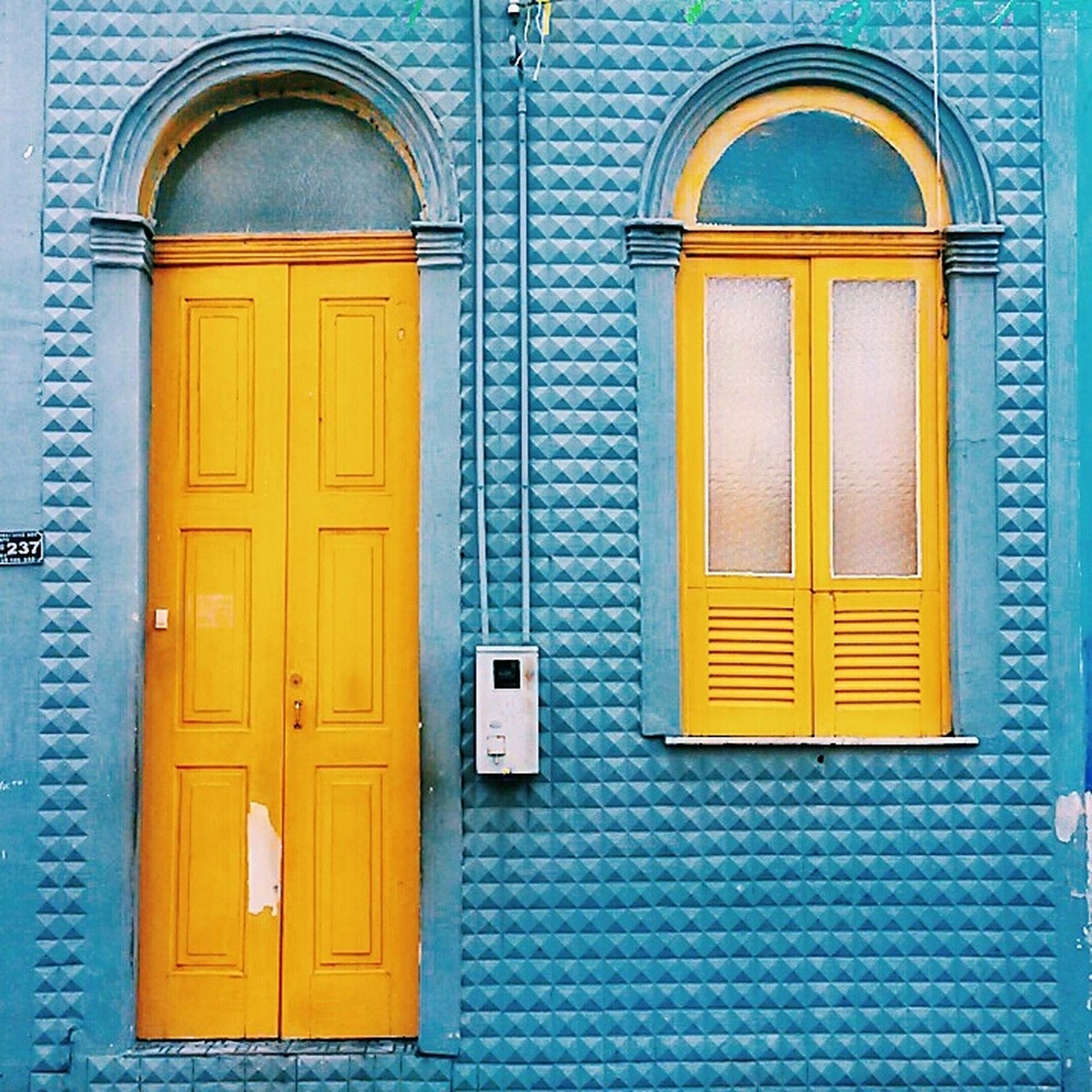 window, building exterior, closed, architecture, door, built structure, yellow, arch, house, entrance, protection, safety, residential structure, facade, residential building, outdoors, day, security, shutter, wood - material