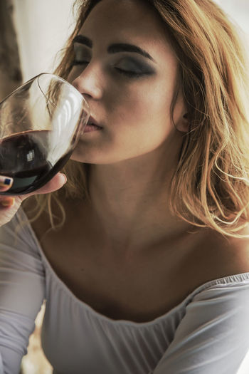 Refreshment Drink Food And Drink Wine Real People One Person Lifestyles Alcohol Wineglass Glass Women Young Women Holding Young Adult Indoors  Front View Leisure Activity Adult Drinking Red Wine Hairstyle