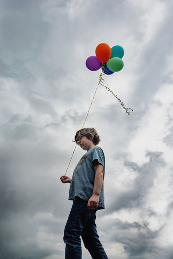 Low angle view of boy holding balloons against sky