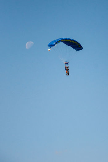 Moon Adventure Blue Clear Sky Day Exhilaration Extreme Sports Flying Freedom Joy Leisure Activity Low Angle View Mid-air Nature Outdoors Parachute Real People Sky Skydiving Sport Tandem Jump Unrecognizable Person