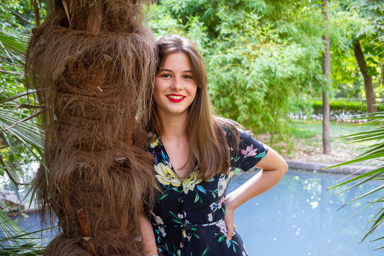 Portrait of a smiling young woman against trees
